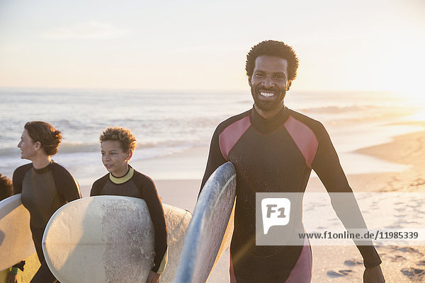 Portrait lächelnder  selbstbewusster Surfer mit Surfbrett und Familie am sonnigen Sommer-Sonnenuntergangstrand.