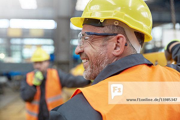 Profil lächelnder Arbeiter in der Fabrik