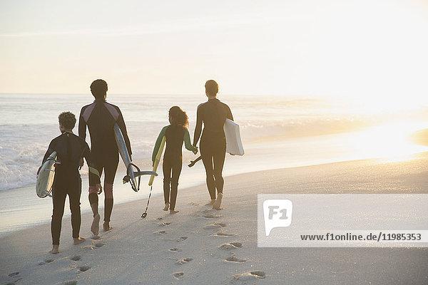 Familie im Neoprenanzug mit Surfbrettern am sonnigen Sommer-Sonnenuntergangsstrand