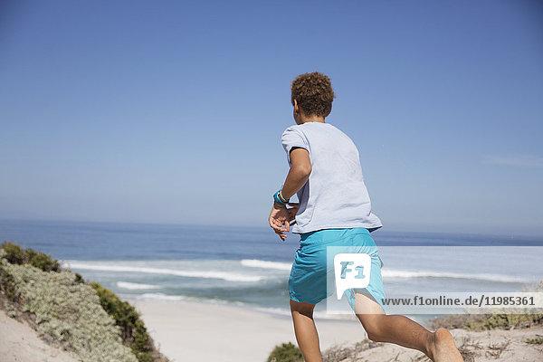Vorjugendlicher Junge  der am sonnigen Sommerstrand läuft.
