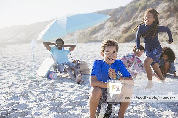 Portrait lächelnder vorpubertärer Junge trinkt Saft am sonnigen Sommerstrand mit Familie