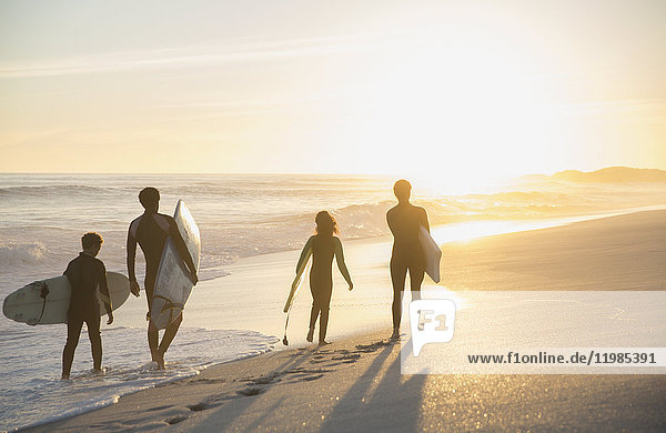 Familien-Surfer wandern mit Surfbrettern am sonnigen Sommer-Sonnenuntergangsstrand