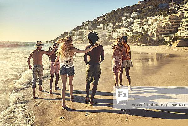 Junge Pärchenfreunde beim Spaziergang am sonnigen Sommerstrand