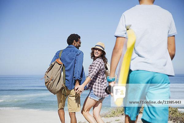 Familienwanderung mit Boogie-Board am sonnigen Sommerstrand des Ozeans