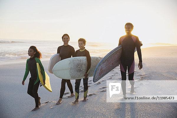 Familien-Surfer mit Surfbrettern am Sommer-Sonnenuntergangsstrand