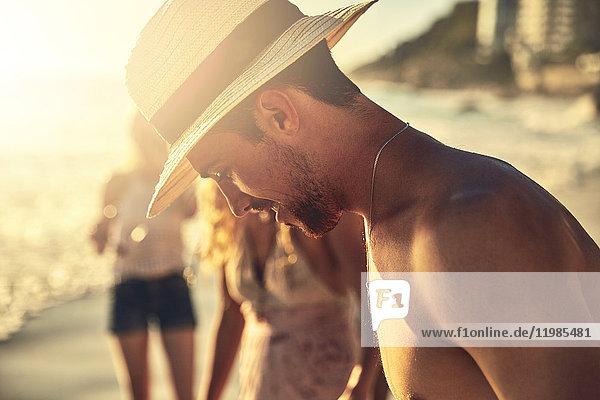 Junger Mann mit Strohhut und Blick auf den sonnigen Sommerstrand