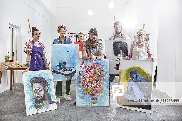 Porträt von selbstbewussten Künstlern  die Bilder im Atelier der Kunstklasse zeigen