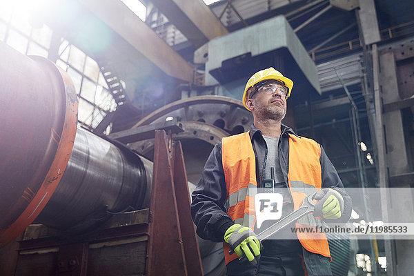 Zuversichtlicher Arbeiter mit Schraubenschlüssel in der Fabrik