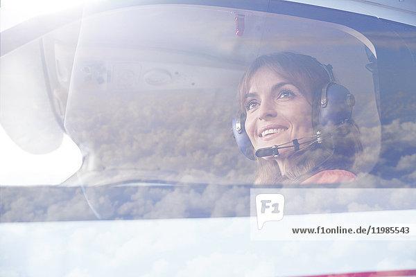 Lächelnde Pilotin fliegt Flugzeug im Cockpit
