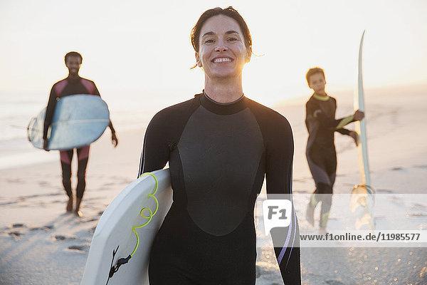Portrait lächelnde Surferin im Neoprenanzug mit Surfbrett und Familie am sonnigen Sommerstrand