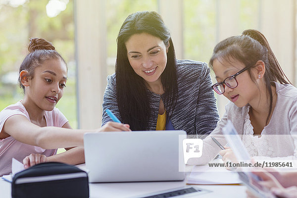 Lehrerinnen und Schülerinnen recherchieren am Laptop in der Bibliothek