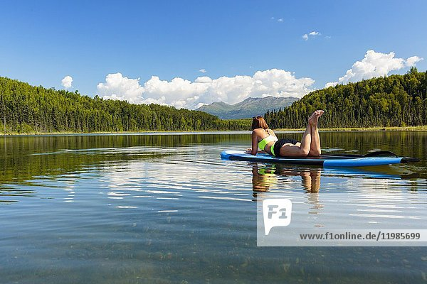 Woman relaxing on stand up paddle board on lake.