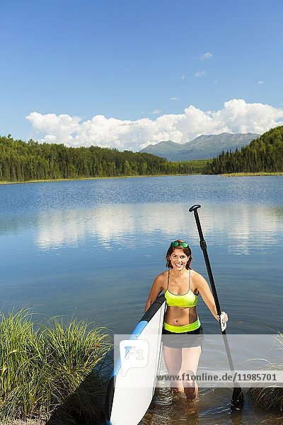Woman carries stand up paddle board as she exits the lake.