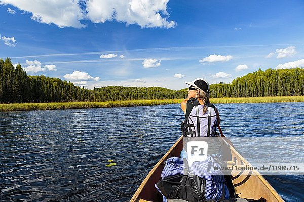 Woman paddling in bow of canoe on calm lake.