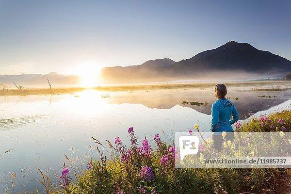 Woman watching sunrise at a calm  roadside lake along Turnagain Arm.