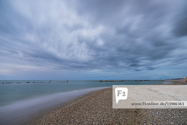 Storm clouds are reflected in the clear water at dusk Porto Recanati Province of Macerata Conero Riviera Marche Italy Europe.