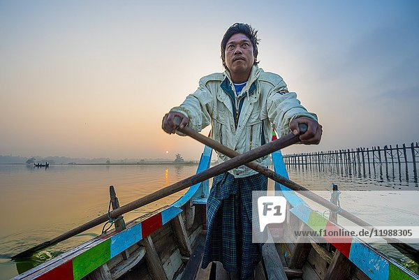 Amarapura  Mandalay region  Myanmar. Man rowing on his colorful boat on the Taungthaman lake at sunrise  with the U Bein bridge in the background.