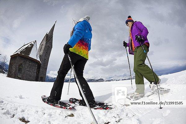 Chicas excursionistas con raquetas de nieve en las inmediaciones de la iglesia de madera de Windegg.
