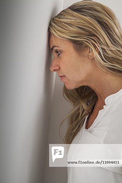 Young blonde woman's head leaning against a wall.