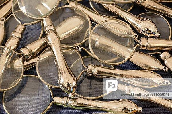 Heap of vintage magnifying glasses on sale in bric-a-brac antiques street market  shot at Mediterranean little town of Chiavari  Genova  Liguria  Italy. Heap of vintage magnifying glasses on sale in bric-a-brac antiques street market, shot at Mediterranean little town of Chiavari, Genova, Liguria, Italy.
