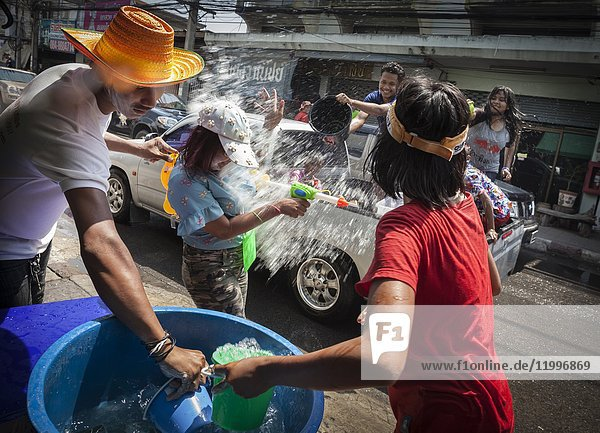 Songkran in Phimai  city streets are filled with people and cars with lots of people having fun with the Thai New Year celebrations. Phimai  Thailand  Asia.