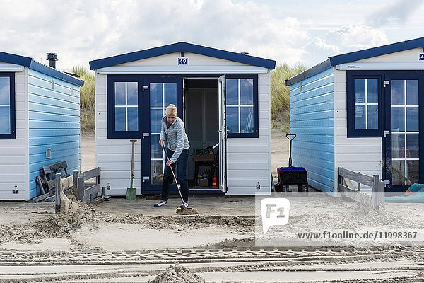 Hook of Holland  Netherlands. Mature adult woman sweeping the front yard of her little beach house free of sand.