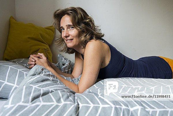 Tilburg  Netherlands. Blonde adult woman hanging around her Airbnb guestroom bed.