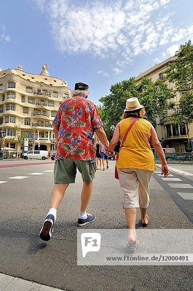 Couple walking. Mila house aka 'La Pedrera' 1906-1912. 261-265 Provença street. Architect Antoni Gaudí. Barcelona. Catalonia. Spain