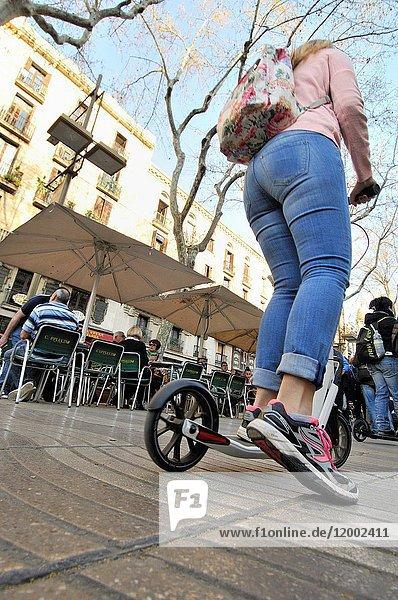 Girl in a Kick scooter. Barcelona  Catalonia  Spain.