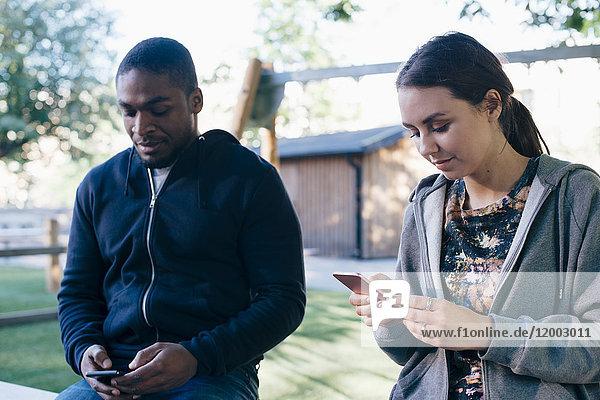 Junge multiethnische Freunde mit Smartphones