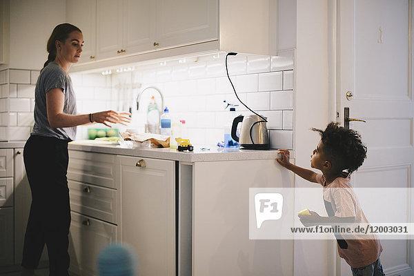 Junge schaut Mutter an  die in der beleuchteten Küche arbeitet.