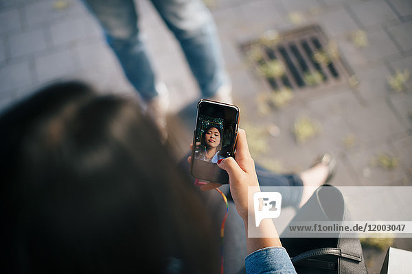 High angle view of teenage girl taking selfie from smart phone in city