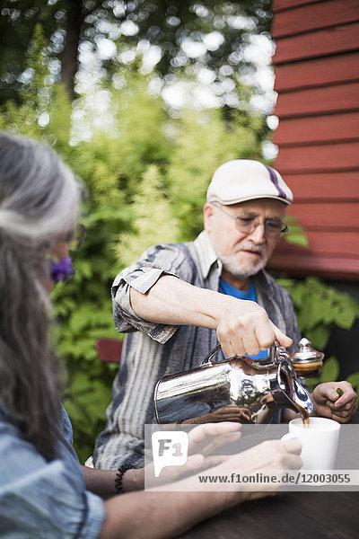 Senior Mann gießt Kaffee in Tasse für Frau im Hinterhof