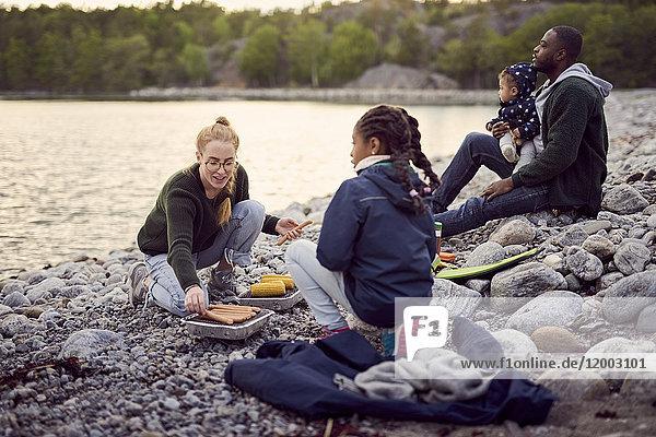 Mutter beim Zubereiten von Speisen auf dem Grill inmitten einer Familie  die während des Campings auf Steinen am Strand sitzt.