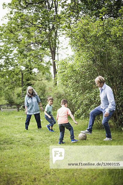 Familie spielt Fußball im Hinterhof