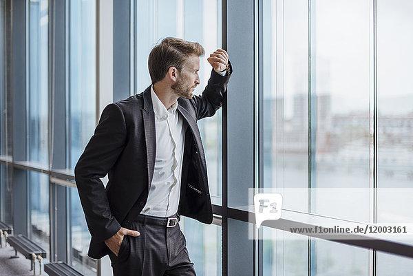 Geschäftsmann steht im Büro und schaut aus dem Fenster.