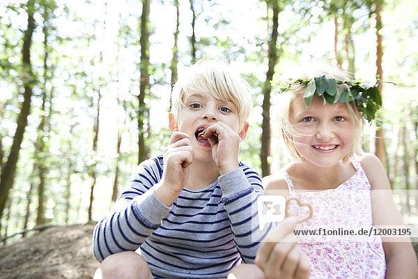 Junge und Mädchen im Wald essen Herzbrezelgebäck