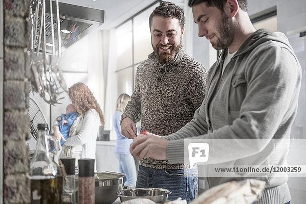 Zwei Männer mit Familie bei der Zubereitung einer Mahlzeit in der Küche