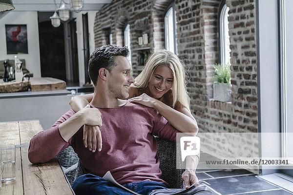 Glückliches Paar in der Landhausküche  Zeitung lesen