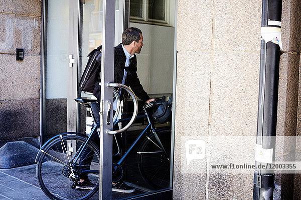 Geschäftsmann mit Fahrradeingang in der Stadt