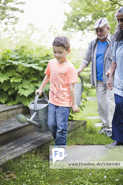 Boy carrying watering can with grandparents walking in back yard
