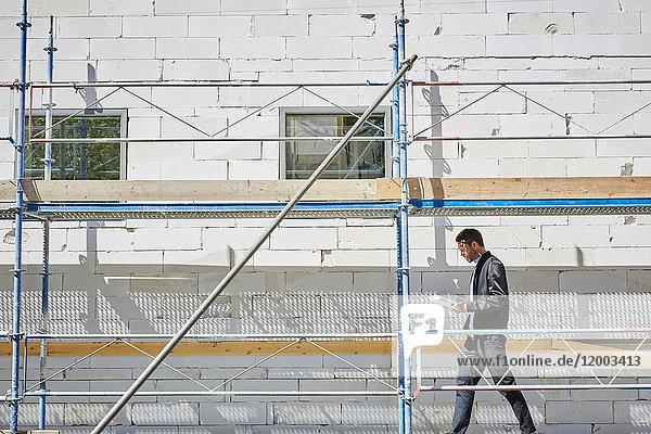 Seitenansicht eines Geschäftsmannes mit Bauplan  der an einem sonnigen Tag an einem unvollständigen Gebäude spazieren geht.