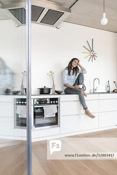 Lächelnde Frau entspannt in der Küche zu Hause