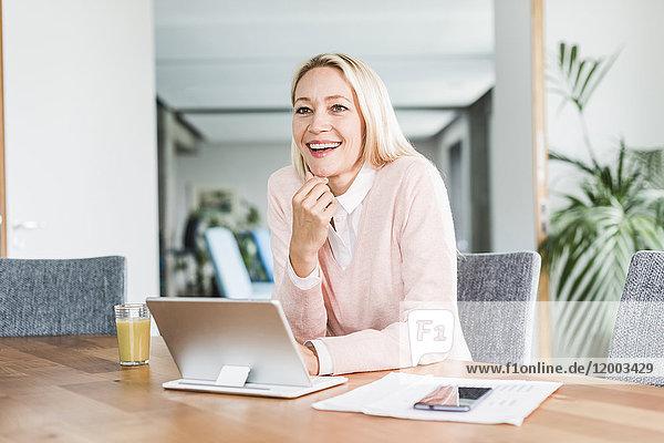 Lächelnde Geschäftsfrau mit Tablette im Büro