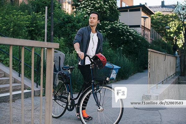 Mittlerer Erwachsener Mann  der mit dem Fahrrad auf einem Fußweg in der Stadt spazieren geht.