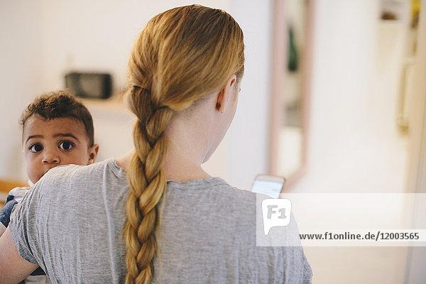 Rückansicht der Mutter mit geflochtenem Haar  die den Sohn zu Hause trägt.