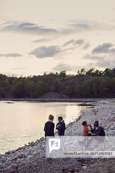 Familiencamping am Strand gegen den Himmel bei Sonnenuntergang