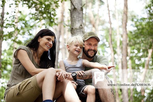 Glückliche Familie mit Sohn im Wald sitzend