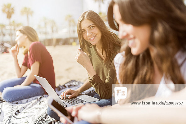 Porträt der lächelnden jungen Frau mit Freunden am Strand mit Laptop