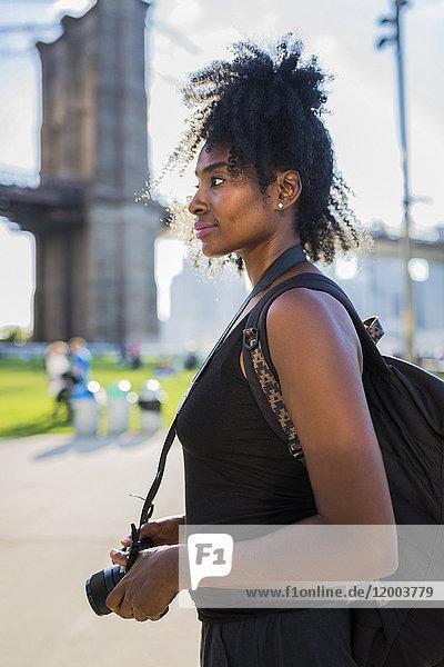 USA,  New York City,  Brooklyn,  Frau mit Kamera an der Brooklyn Bridge